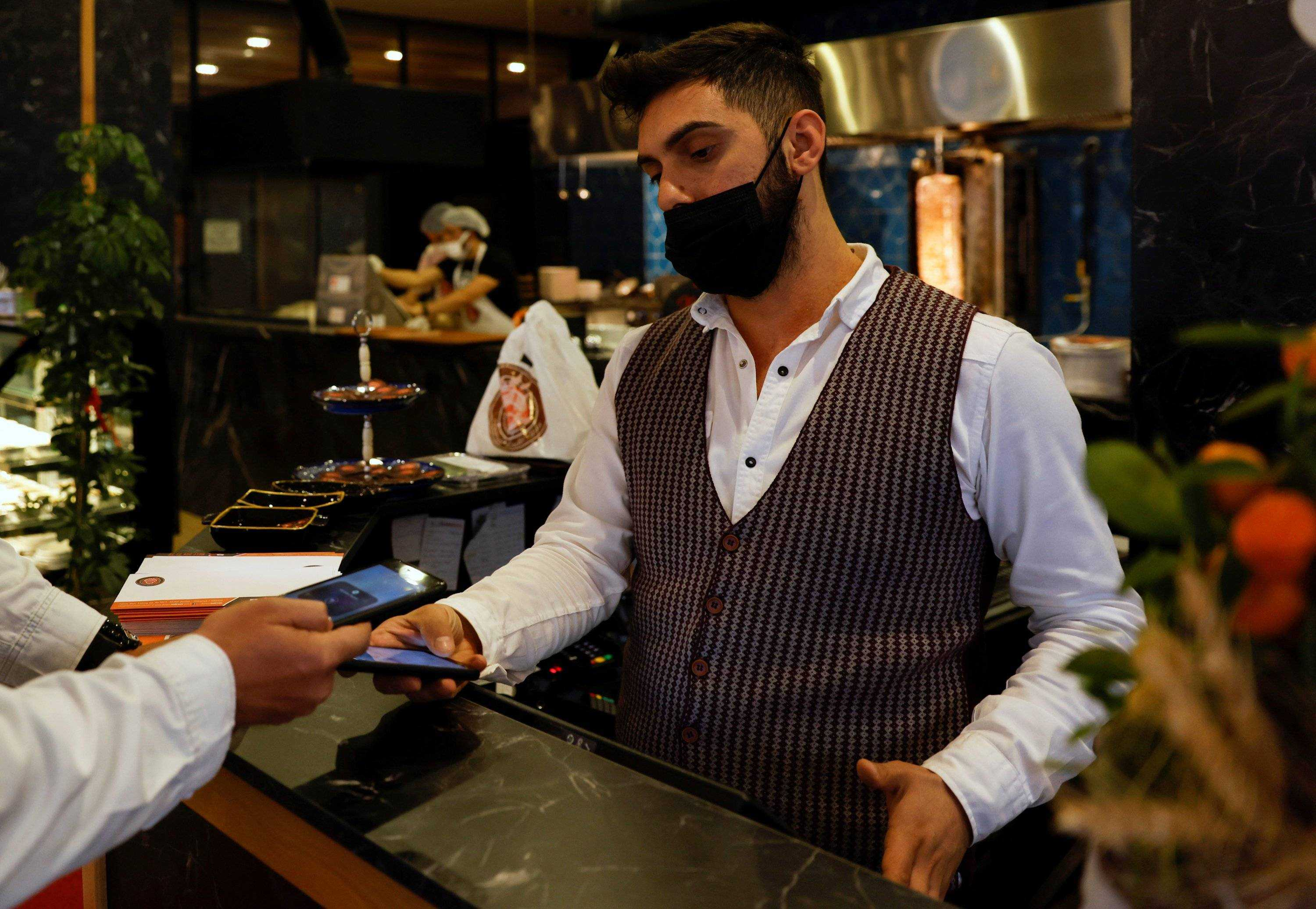 A cashier accepts payment through a cryptocurrency app at a kebab restaurant that accepts Bitcoin and Dexchain in Istanbul, Turkey on April 27, 2021 (Photo Reuters)
